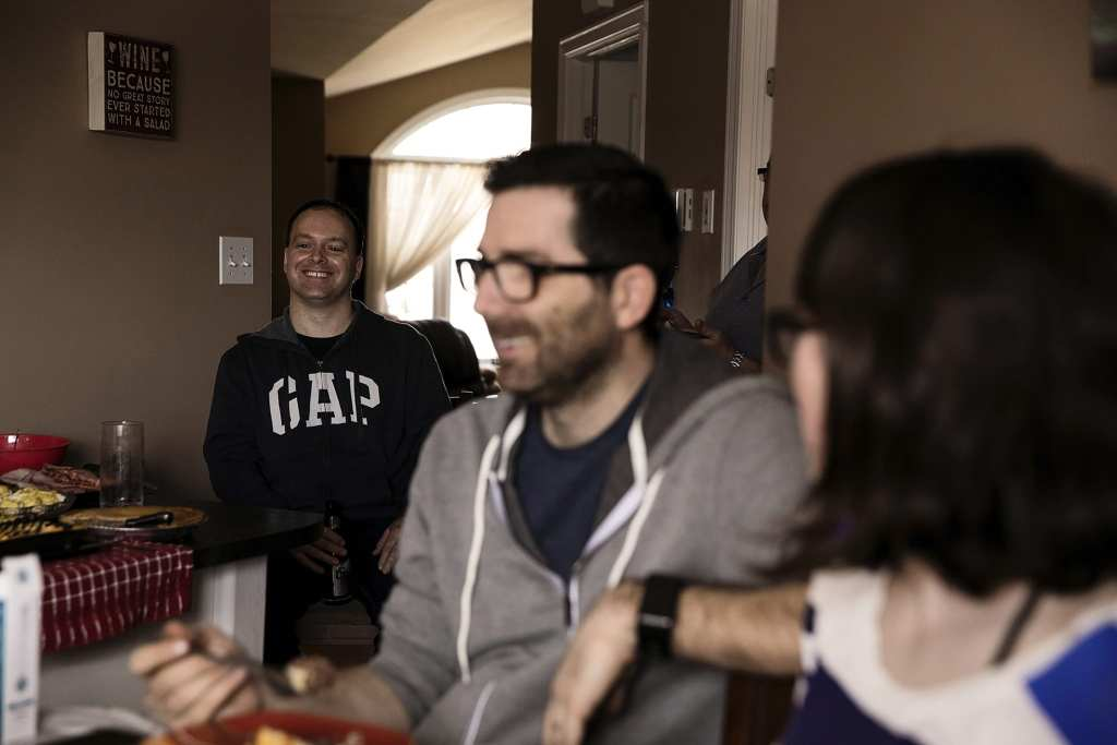 man laughing in background with family