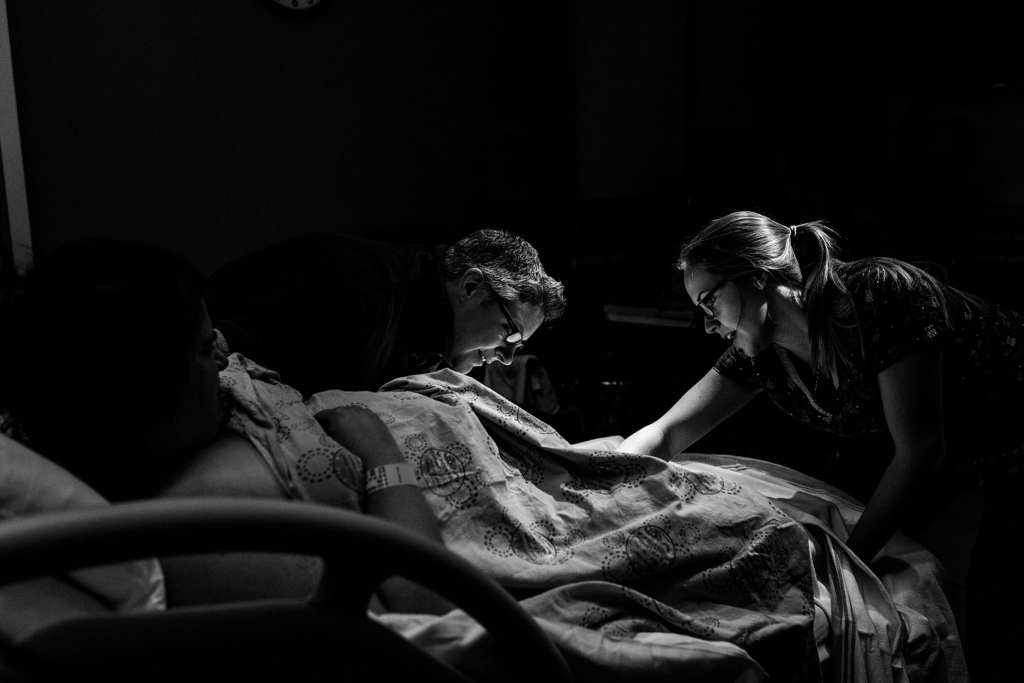 nurse and wife check on labouring mom in hospital bed
