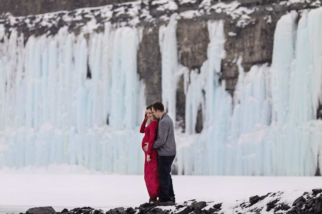 pregnant woman in red dress is held by husband with frozen waterfall in background