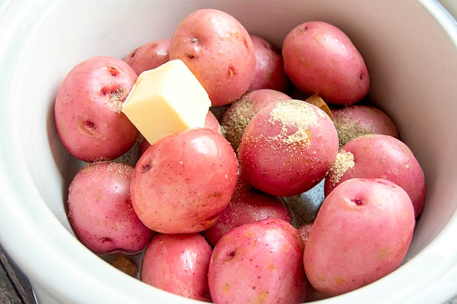 red potatoes in a slow cooker with butter and spices