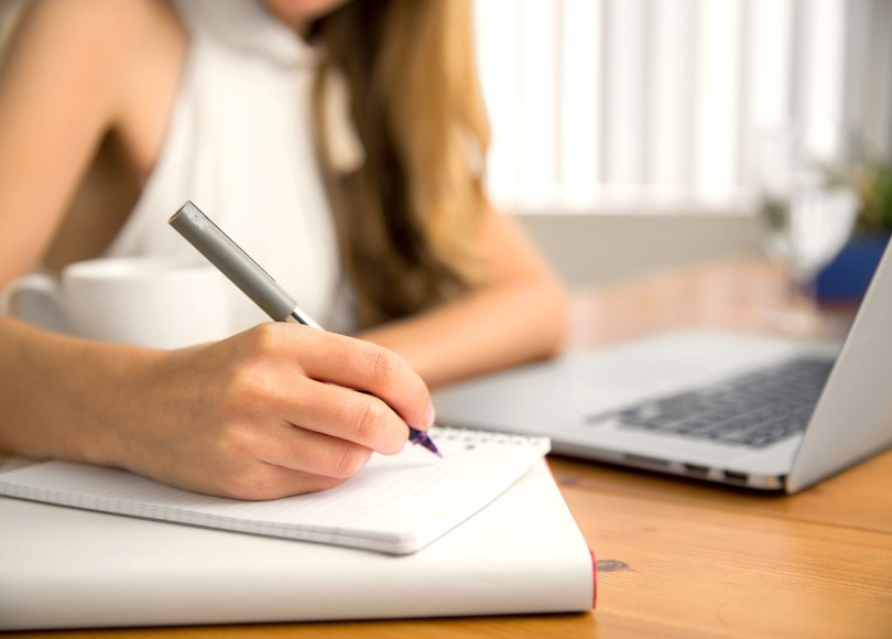 Woman writing blog in notebook with computer nearby