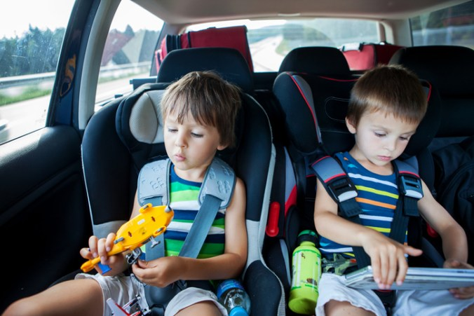 two boys on a road trip playing with toys