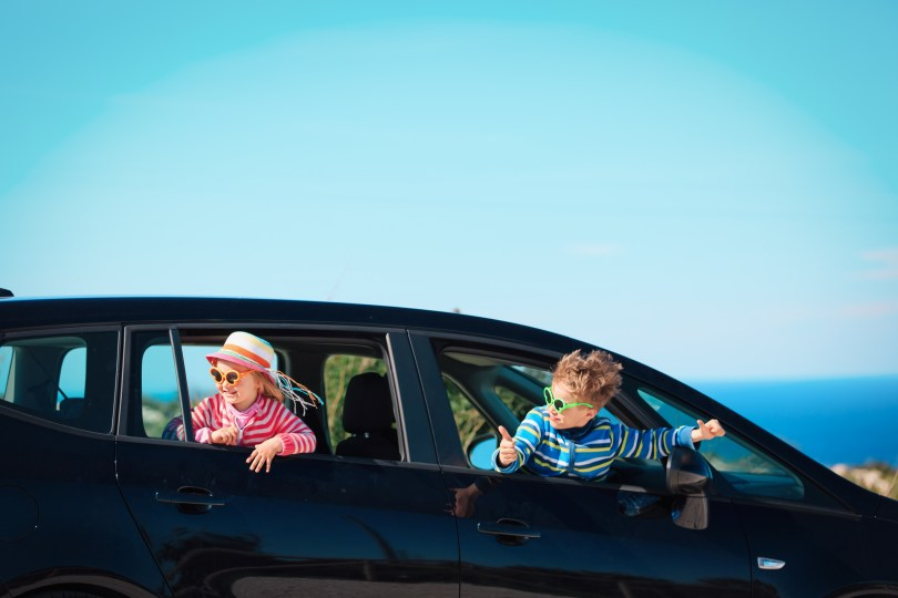 happy little boy and girl enjoy travel by car at sea