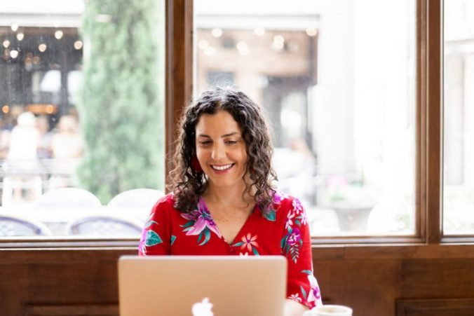 a mom writing with a smile on her computer because she found her passion
