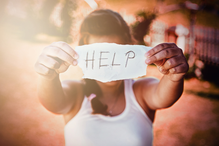 Anxious mom holding up sign for help