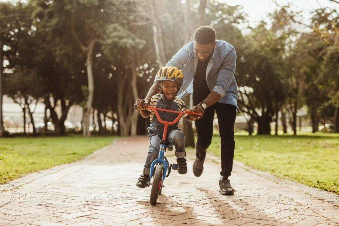 Dad teaching his kid to ride a bike