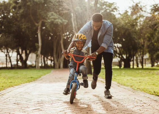Dad teaching his kid to ride a bike