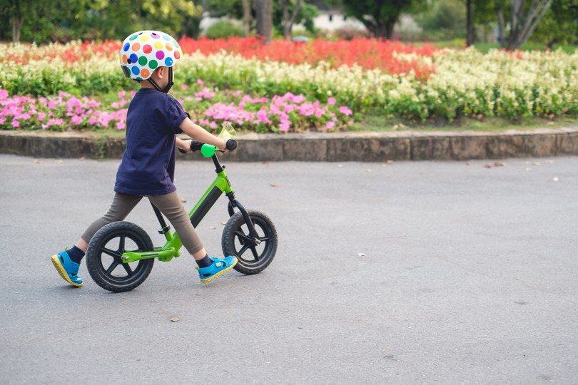 kid who is being taught how to ride a bike without pedals