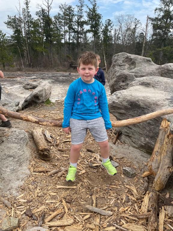 child sitting on tree limb on Arabia Mountain hiking trail