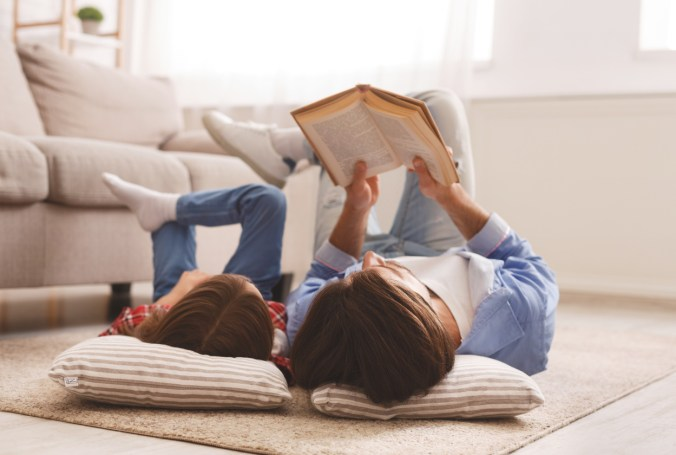 parent encouraging child to love reading by laying on floor looking at book together