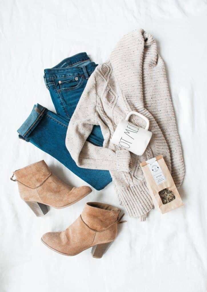 flat lay photo of boots sweater and jeans