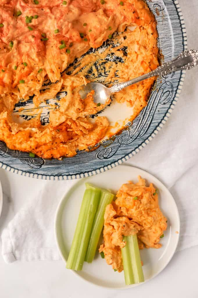buffalo chicken dip with celery on a white plate