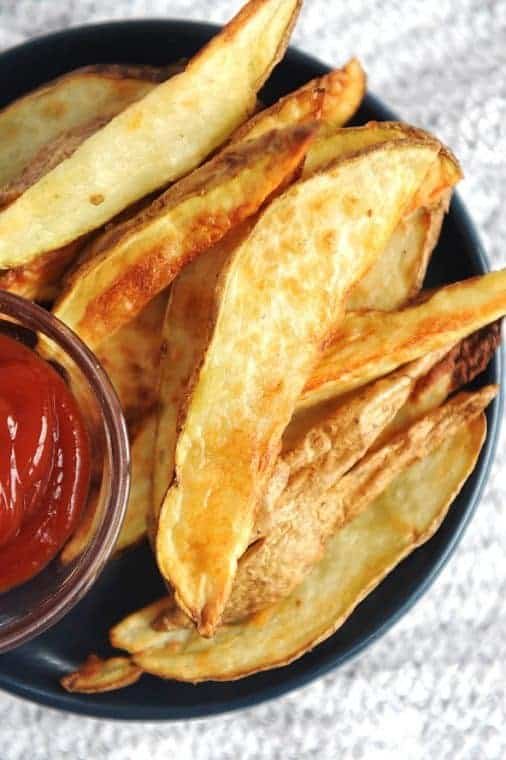 air fryer potato wedges on a plate with ketchup