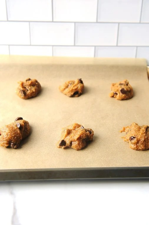 chocolate chip cookie dough on a sheet pan to be baked in the oven