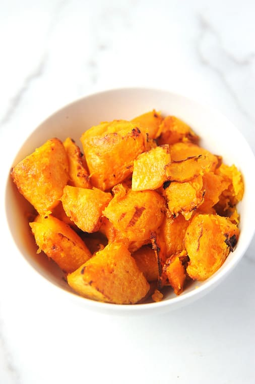 healthy air fryer butternut squash cubes. vegan air fryer butternut squash with simple ingredients. savory and delicious to eat in a fall harvest salad or with brussel sprouts.