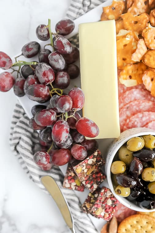 How to Make an Epic ALDI charcuterie board for under $25. Momma Fit Lyndsey gives ideas and a shopping list for what you need to create a cheap cheeseboard on a budget using aldi meat and cheese, aldi cured meats and aldi cheese to make an easy diy charcuterie for two, for four or your entire party.