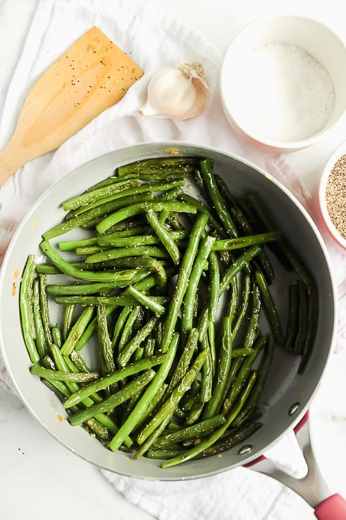 Stove Top Garlic Green Beans with only 4 ingredients! Blanched and then sauteed in olive oil, this healthy green bean recipe by Momma Fit Lyndsey for blistered green beans is easy enough for weeknight veggie sides or fancy enough for Thanksgiving sides or Christmas! Fresh or frozen green beans can be used to get delicious crispy green beans in the skillet.