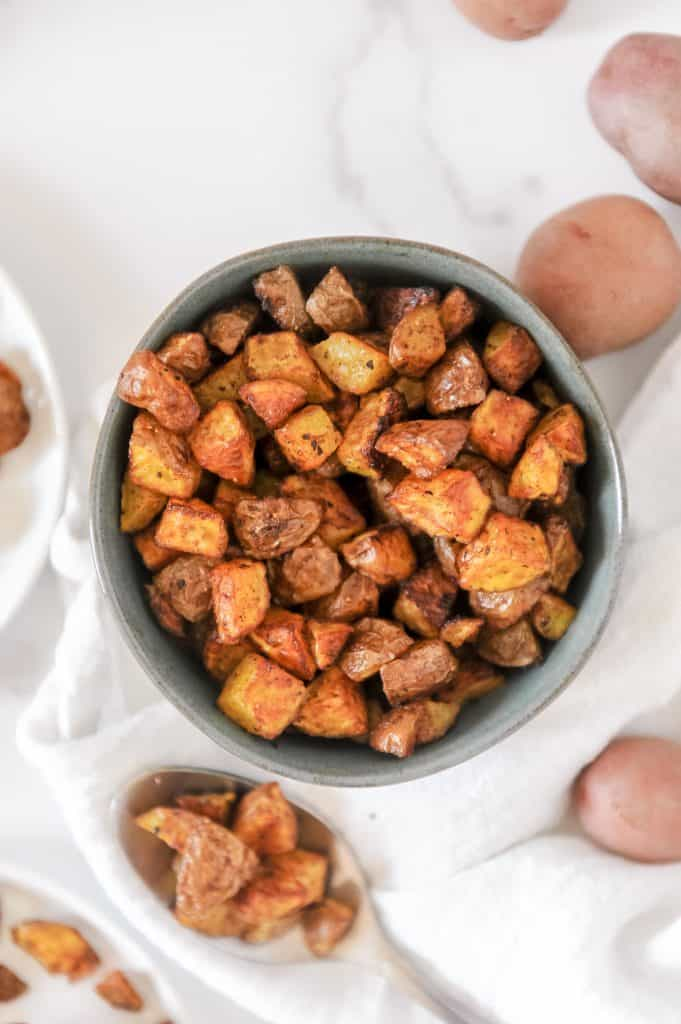 Easy healthy air fryer breakfast potatoes recipe made with red baby potato cubes. Momma Fit Lyndsey brings you this paleo and whole30 friendly breakfast potato recipe. Check out the video for more!
