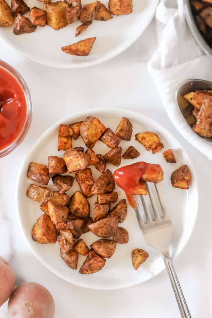 plate of breakfast potatoes with ketchup