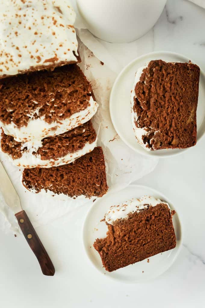 ginger banana bread with cream cheese frosting on a plate
