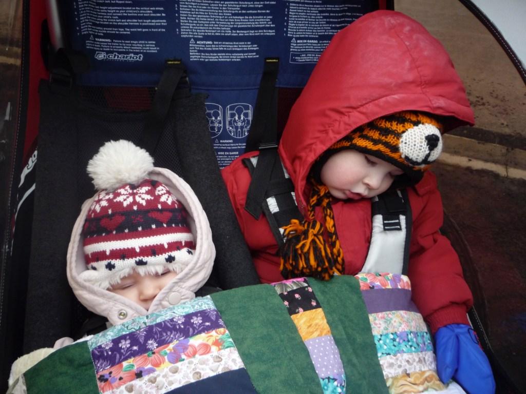 Kids asleep in stroller.