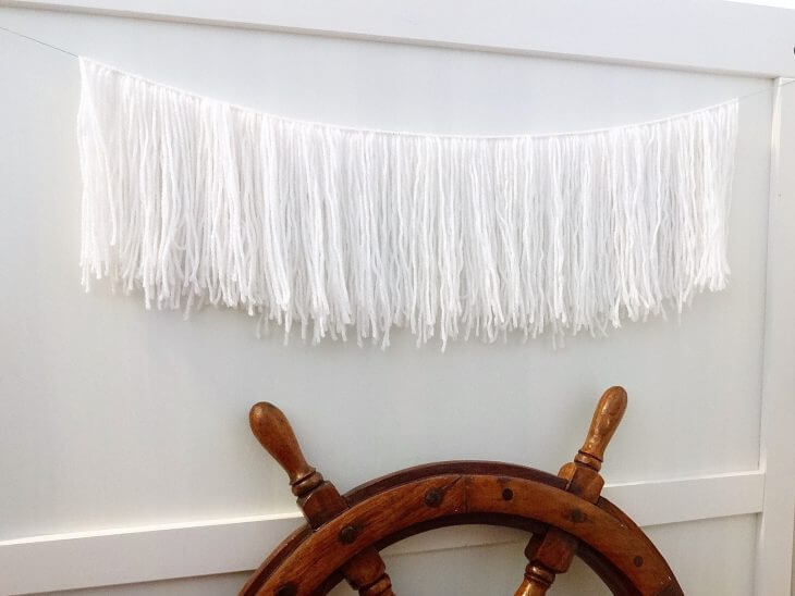 How to make a simple yarn garland wall art to add some texture. #yarngarland #garland #texturedgarland | mommygonetropical.com