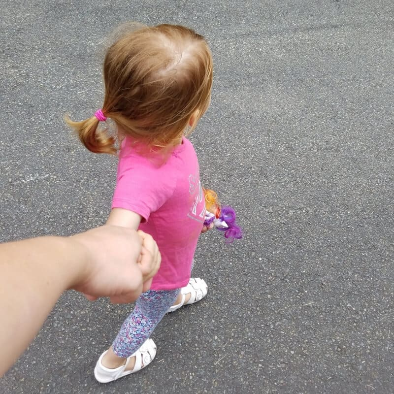 Toddler holding moms hand