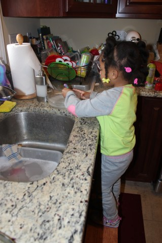 Quinn helping wash dishes