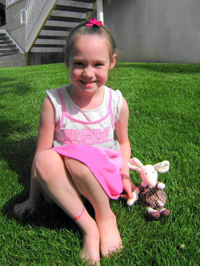 jelly cat mouse plush sitting on grass next to little girl