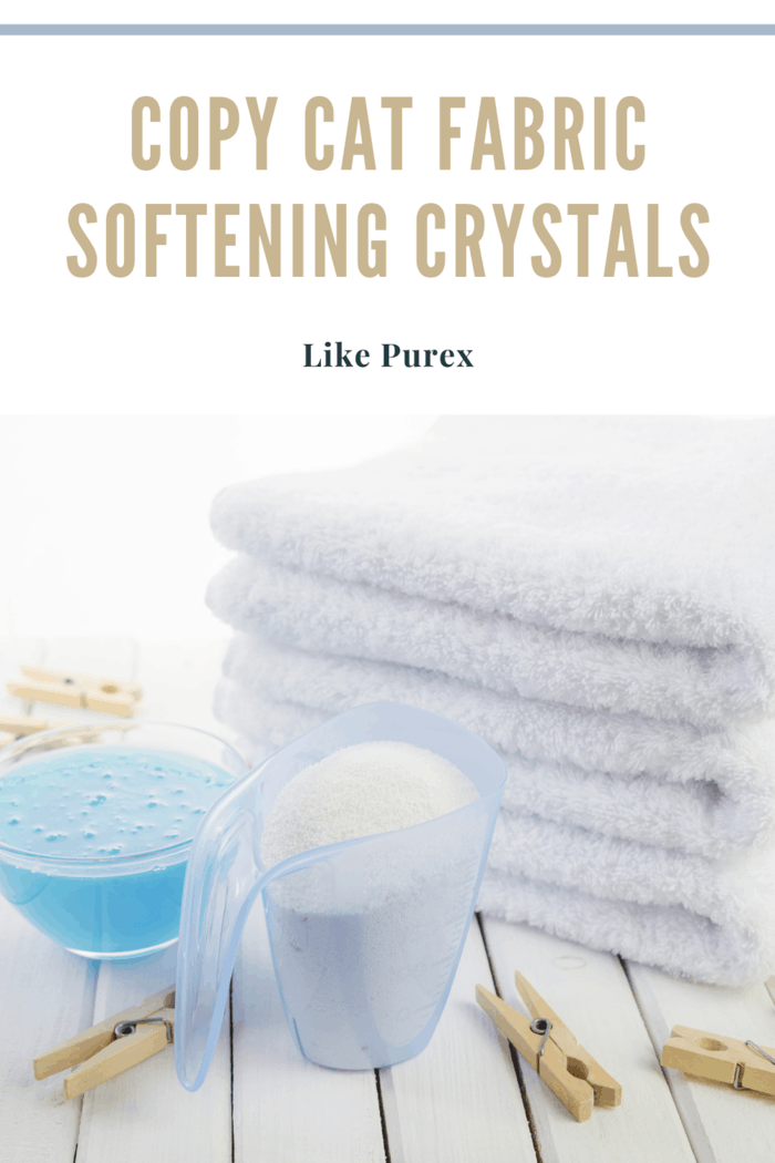 homemade fabric softening crystals in container next to clean white towels that are folded