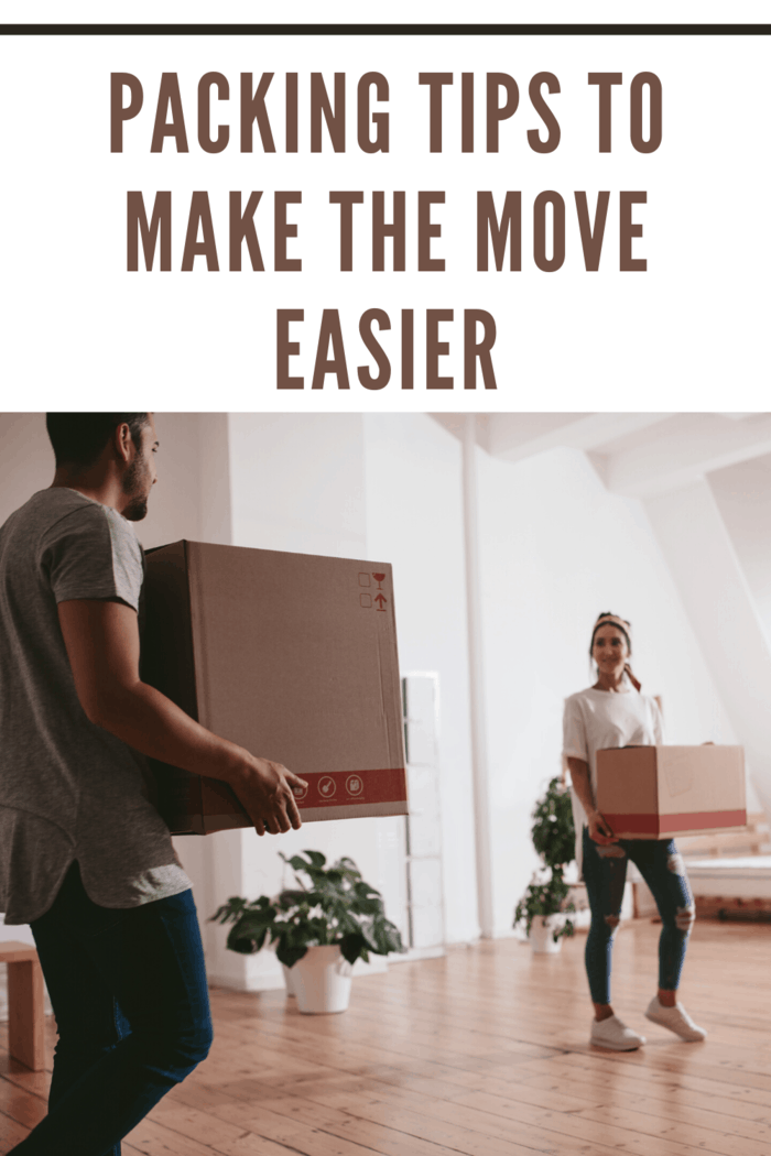 man and woman carrying moving boxes into room