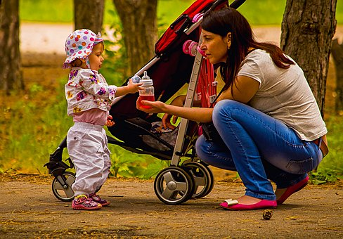 mom with double jogging stroller kneeling down giving toddler a drink