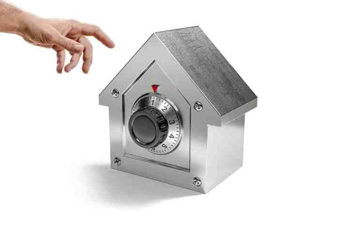 small safe in shape of home with combination lock on front as home security