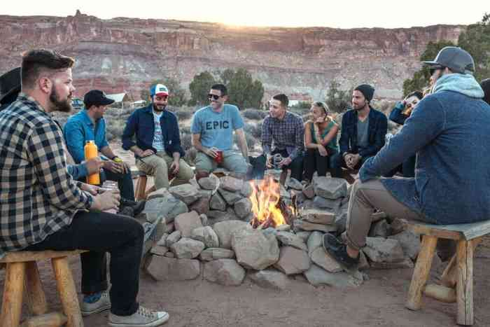 group of adults gathered around a camp fire with cliff mountains behind them