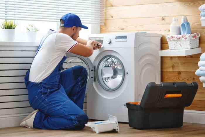 repairman doing appliance repair on washing machine
