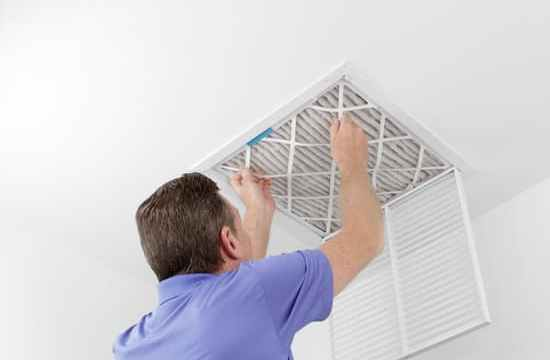 Caucasian male removing a square pleated dirty air filter with both hands from a ceiling air duct. Guy taking out an unclean air filter from a home ceiling air filter