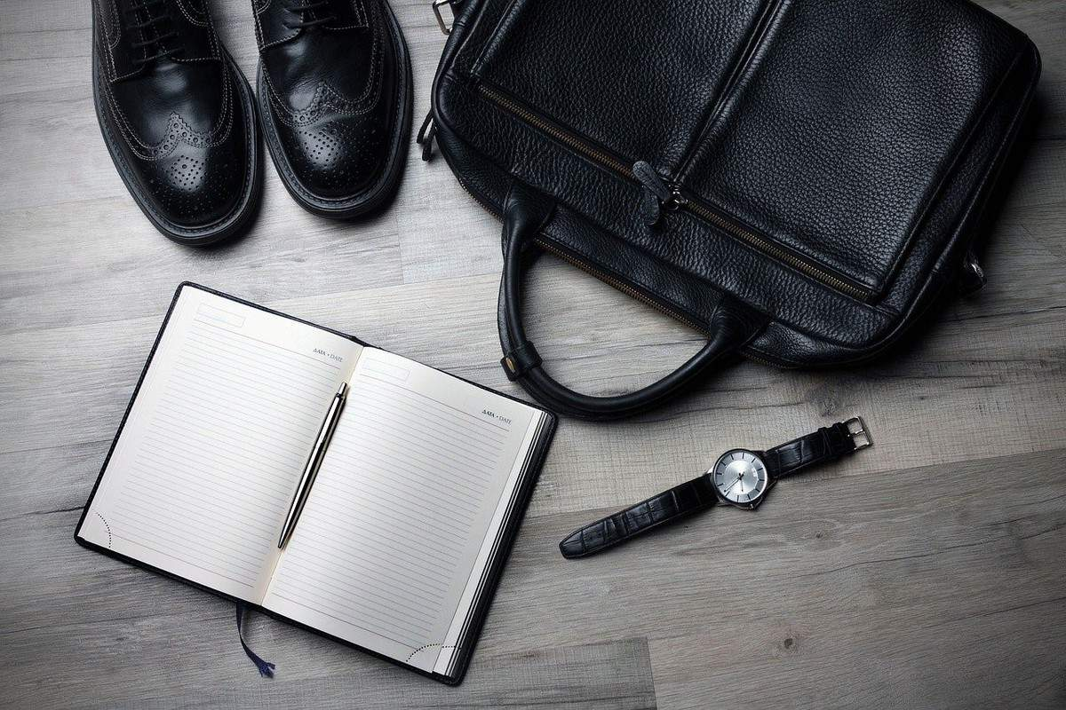 black laptop bag, black men's dress shoes, blank journal and watch with black band premium corporate gifts