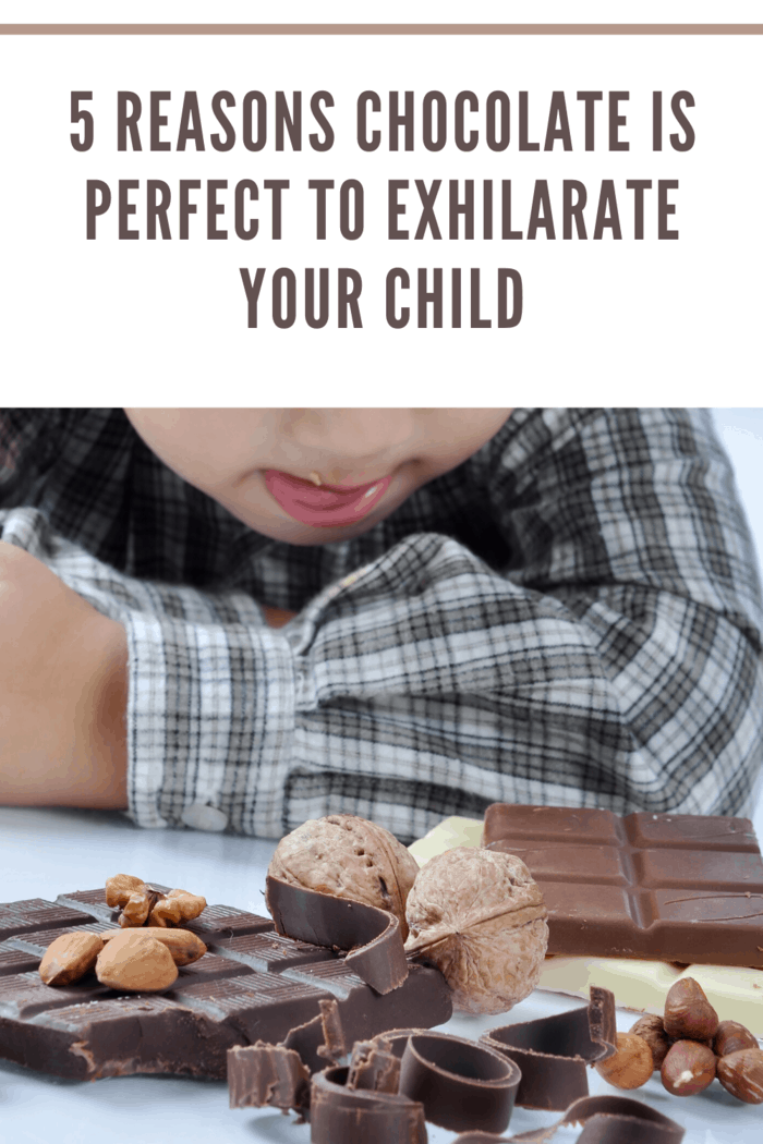 cute boy licking lips staring at assortment of chocolate treats