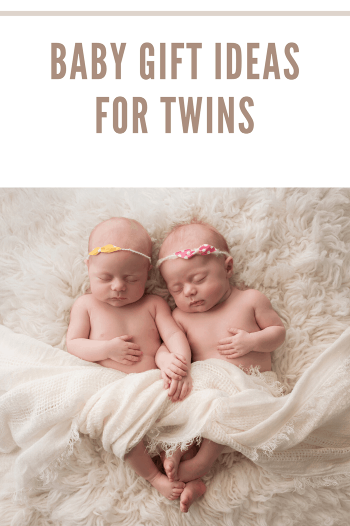 Seven week old fraternal, twin baby girls sleeping on a white flokati rug.
