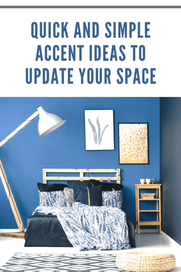 room with blue wall in two shades, tall adjutable lamps, photos on wall, throw blanket draped on bed and basket on floor.