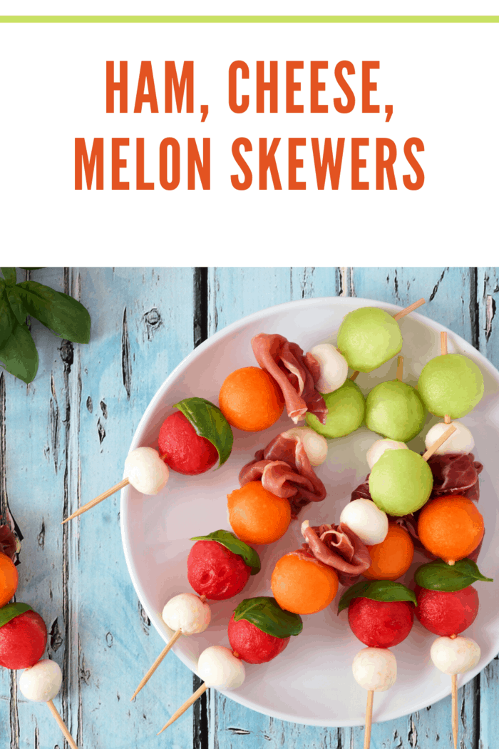 Ham, Cheese, Melon skewers-Plate of delicious summer fruit skewers with melon, cheese and prosciutto on a rustic blue wood background Image