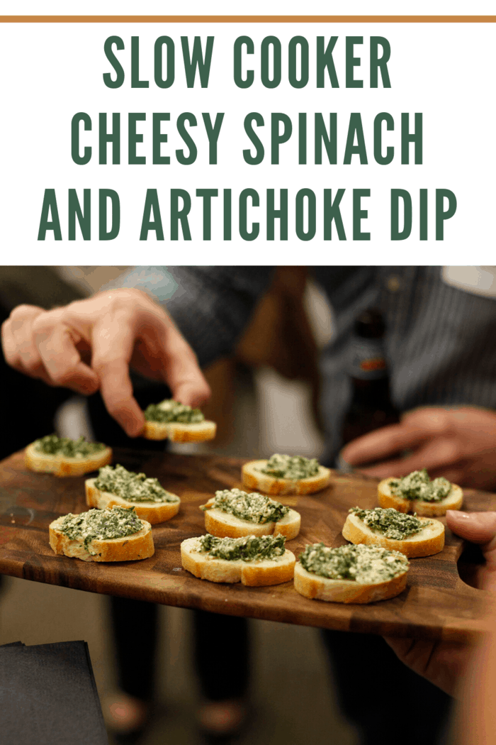 slow cooker cheesy spinach and artichoke dip spread on top of toasted baguettes and being served to guests at a party