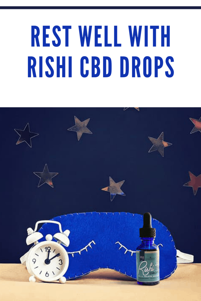 Live Rishi CBD drops nxt to alarm clock and sleep mask with dark blue background with gold stars.