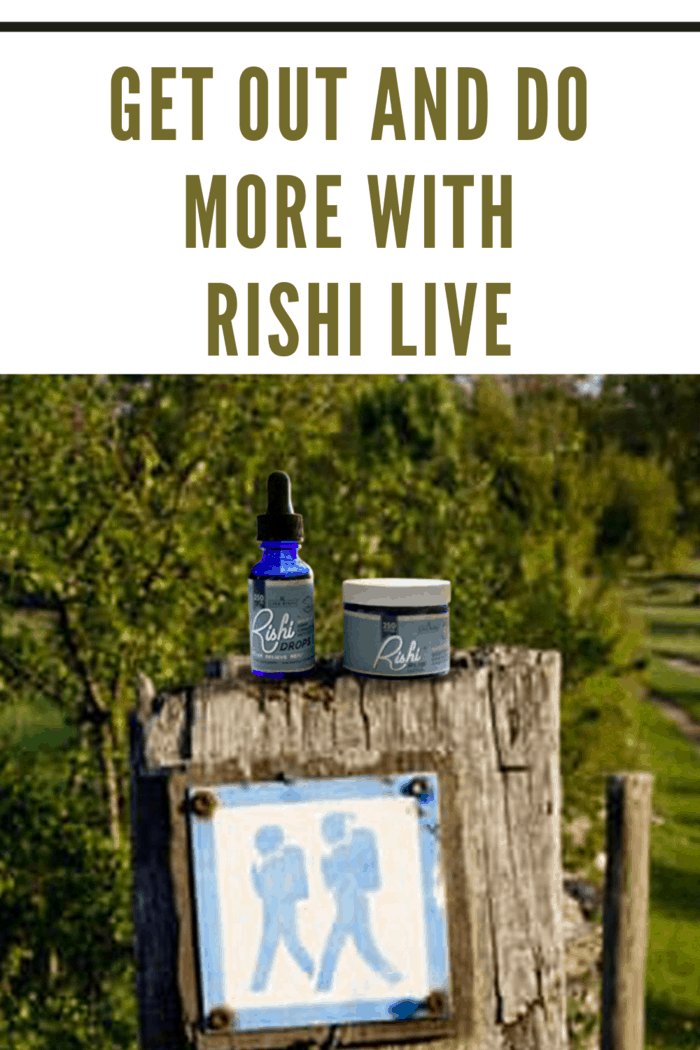rishi rub and rishi drops sitting on a fence post above a hiking sign in the woods.