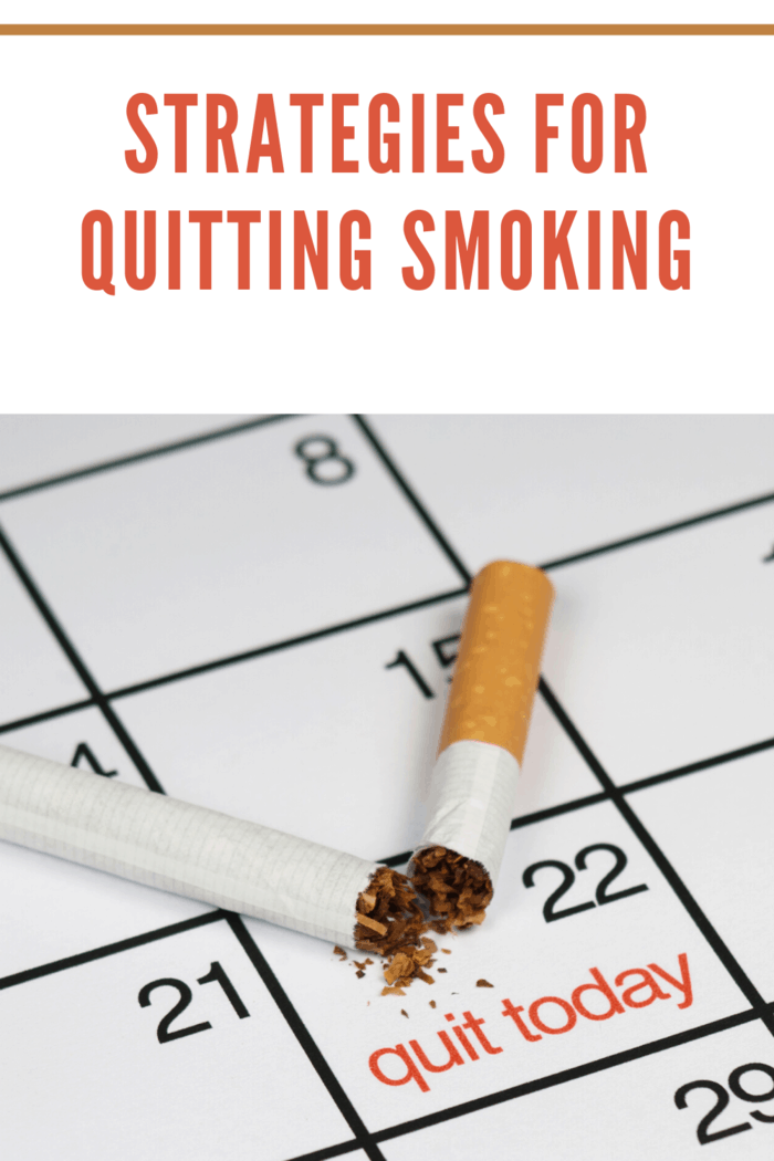 "calendar with the 22 block ""quit smoking"" in red and a broken cigarette laying on top of the calendar square"