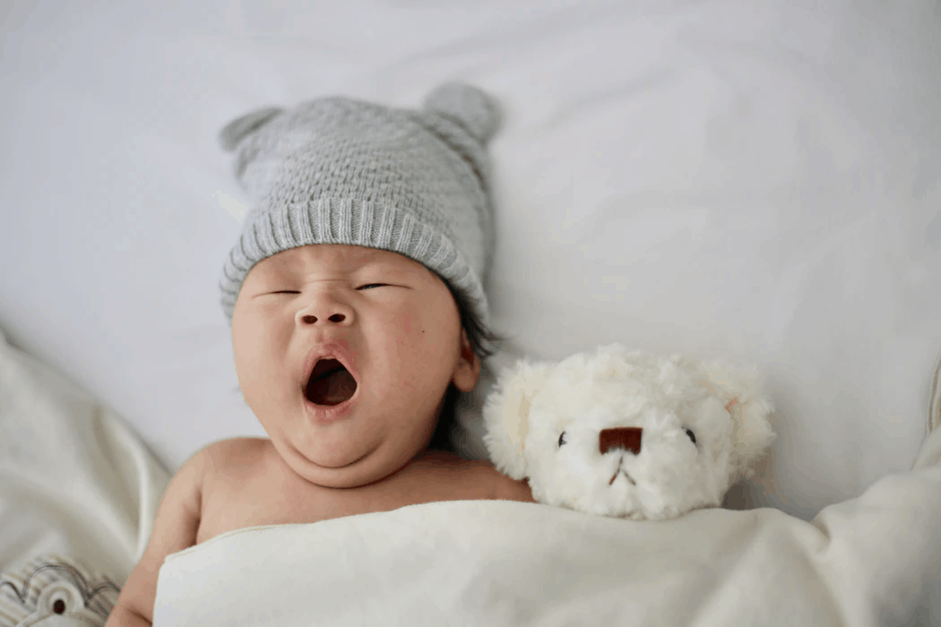 baby with gray bear hat on yawning next to white teddy bear