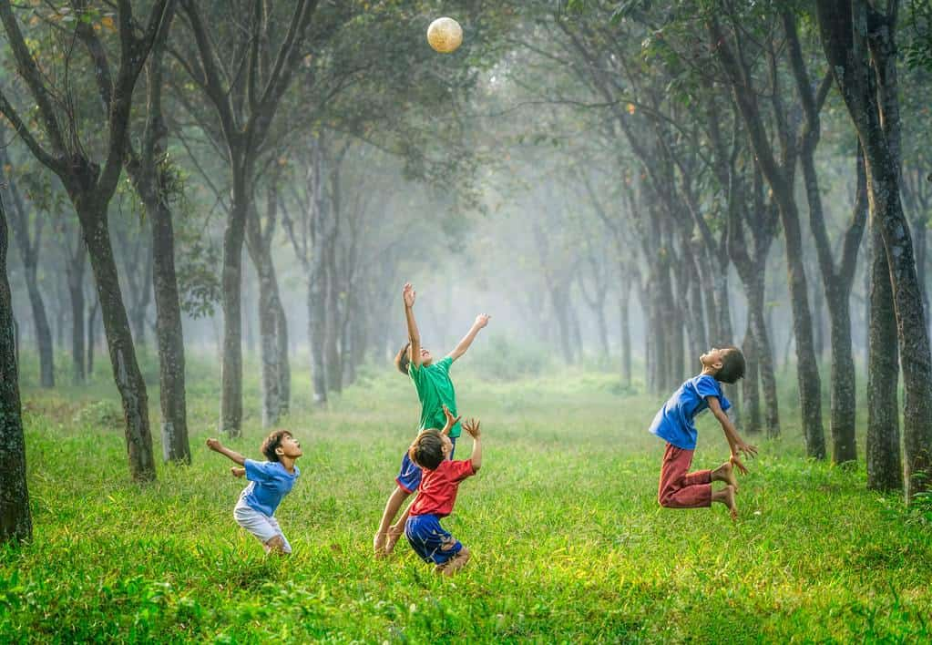 four boys playing soccer in a spring green meadow with trees on either side