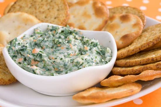 This slow cooker cheesy spinach and artichoke dip artichoke hearts and spinach nestled in a creamy, cheesy sauce with pita crackers on side for dipping