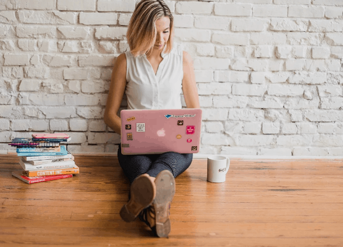 woman leaning against brick wall working on small business marketing from her laptop