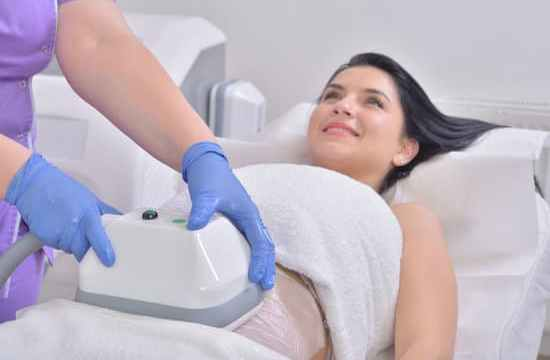 Pretty young woman getting cryolipolyse treatment in professional cosmetic cabinet